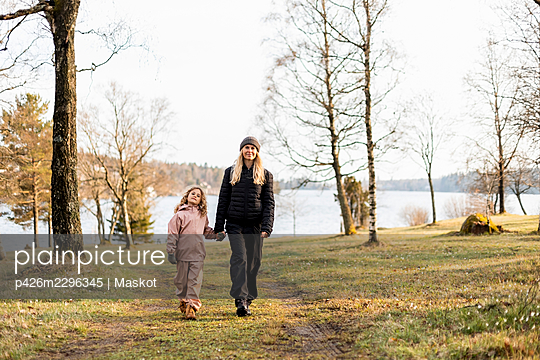 Full length of woman walking with daughter while holding hands at park - p426m2296345 by Maskot