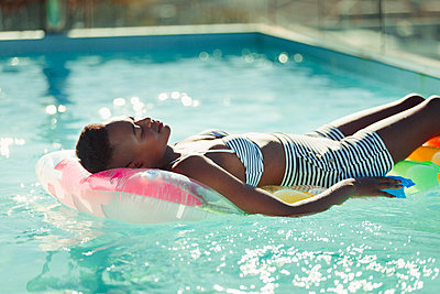 Serene young woman laying on inflatable raft in sunny swimming pool - p1023m2196698 by Paul Bradbury