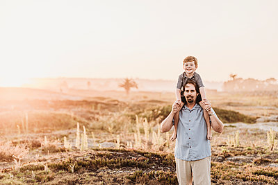 Father holding son up on shoulders while smiling at camera at beach - p1166m2136568 by Cavan Images