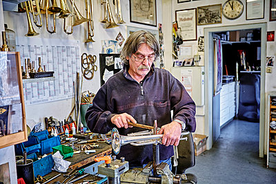 Instrument maker repairing trumpet in workshop - p300m1156964 by Dirk Kittelberger