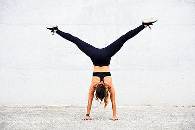 Athlete doing handstand in front of white wall - p300m2060831 von Javier Sánchez Mingorance