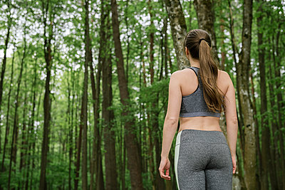 Rear view of young woman wearing sportswear standing in forest - p300m2113894 by Hernandez and Sorokina