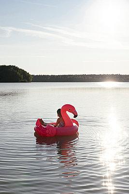 Girl with flamingo pool float on a lake - p300m2143648 by Ekaterina Yakunina