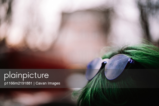 Close up of purple sunglasses on green haired head - p1166m2191881 by Cavan Images