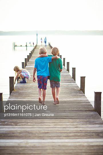 Zwei Jungen laufen Arm in Arm über einen Steg, Starnberger See, Oberbayern, Bayern, Deutschland - p1316m1161075 von Jan Greune