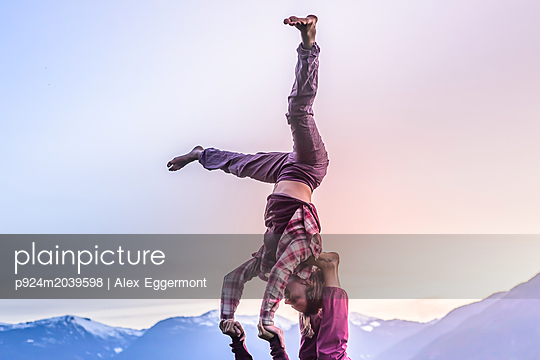 Two young women practicing acroyoga in front of mountain range at sunset, Squamish, British Columbia, Canada - p924m2039598 by Alex Eggermont