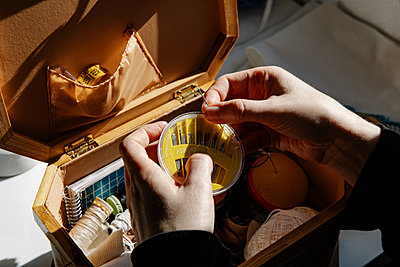 Anonymous tailor female keeps her sewing utensils in a sewing box - p1166m2193824 by Cavan Images