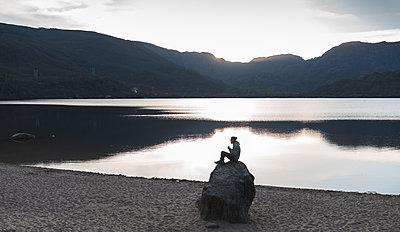 Man sitting on rock near lake during sunset - p300m2282013 by Josu Acosta