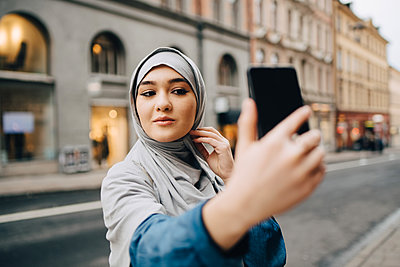 Confident young Muslim woman taking selfie on city street - p426m1556136 by Maskot