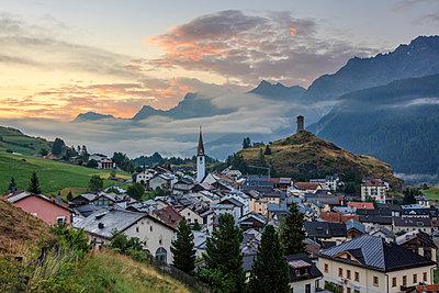 Misty sky on the alpine village of Ardez at sunrise, district of Inn, Lower Engadine, Canton of Graubunden, Switzerland, Europe - p871m1499879 by Roberto Moiola