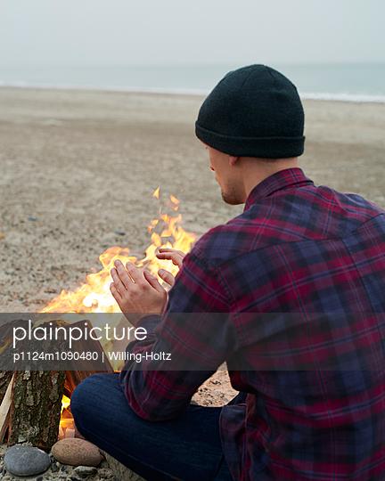 Mann sitzt am Lagerfeuer  - p1124m1090480 von Willing-Holtz
