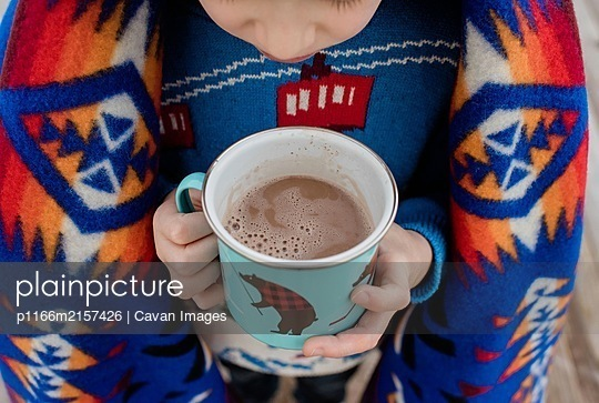 sky view of a boy wrapped in a blanket holding a hot chocolate outside - p1166m2157426 by Cavan Images
