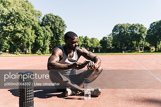 Young athlete sitting on sports field, using smartphone and smartwatch - p300m2004332 von Uwe Umstätter