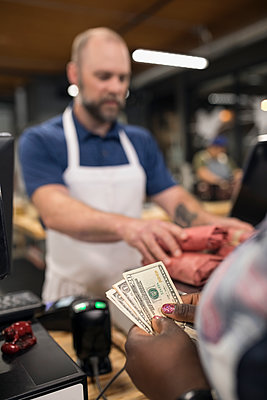 Customer with cash paying butcher in butcher - p1192m1493361 by Hero Images
