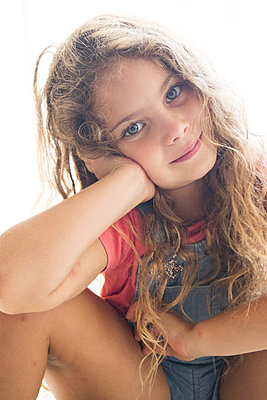 Little girl with curly hair resting head on hand - p1640m2246135 by Holly & John