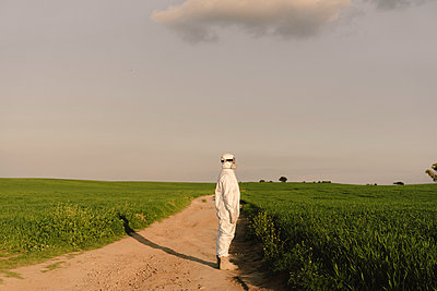 Man wearing protective suit and mask in the countryside - p300m2166402 by Eloisa Ramos