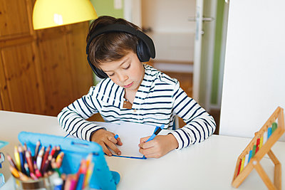 Boy doing homeschooling and writing on notebook, using tablet and headphones at home - p300m2188802 by Epiximages