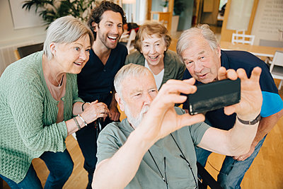 Disabled senior man taking selfie with friends and male nurse at retirement home - p426m2149316 by Maskot