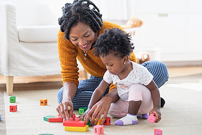 Black mother and baby daughter playing with blocks on carpet - p555m1305423 by JGI/Tom Grill