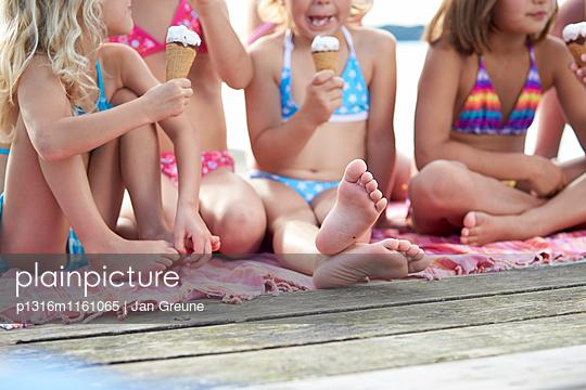Mädchen sitzen auf einem Steg und essen Eis, Starnberger See, Oberbayern, Bayern, Deutschland - p1316m1161065 von Jan Greune