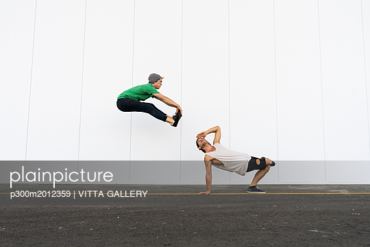 Two acrobats doing tricks together, jumping mid-air - p300m2012359 von VITTA GALLERY