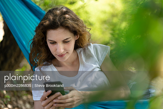 Woman relaxing in hammock and looking on her smartphone in Portugal - p300m2286835 von Steve Brookland