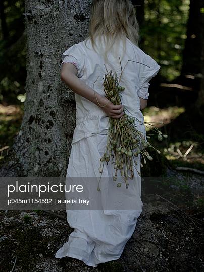 Mädchen versteckt sich hinter einem Baum  - p945m1154592 von aurelia frey