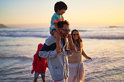 Happy family wading in ocean at sunset - p1023m2200835 by Trevor Adeline