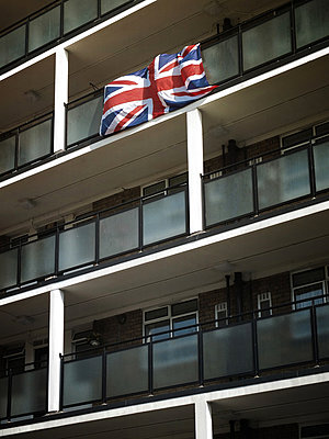 Union Jack flag hanging from a block of flats - p1072m829306 by Neville Mountford-Hoare