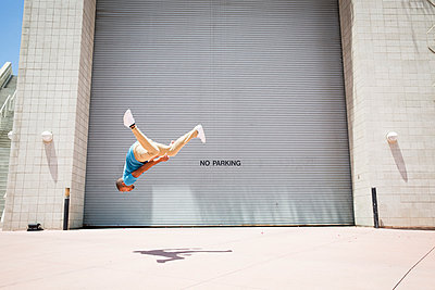 Young man somersaulting in front of a garage door.  - p1100m1038922 by Mint Images