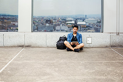 A man sitting on the floor using his smart phone, in front of a viewing point window on to a city.  - p1100m1185884 by Mint Images