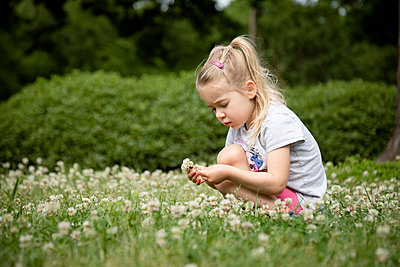 Portrait of a young girl picking flowers in the backyard - p1480m2148178 by Brian W. Downs