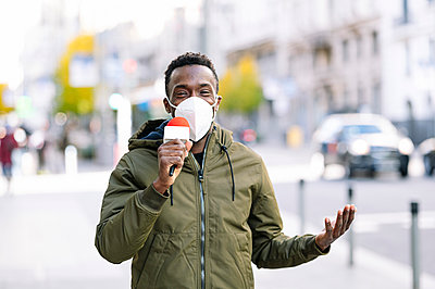 Male presenter wearing face mask talking over microphone while standing in city - p300m2243634 by Jose Luis CARRASCOSA