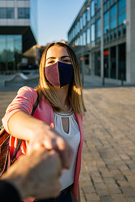 Woman wearing face mask greeting person with a fist bump in the city - p300m2244214 by Xavier Lorenzo
