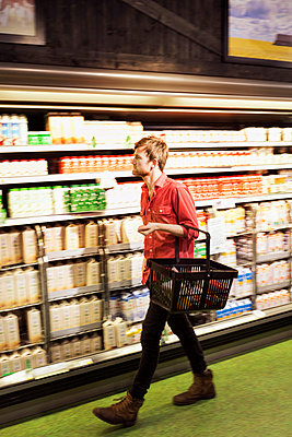 Full length of man shopping at supermarket - p426m1017985f by Maskot