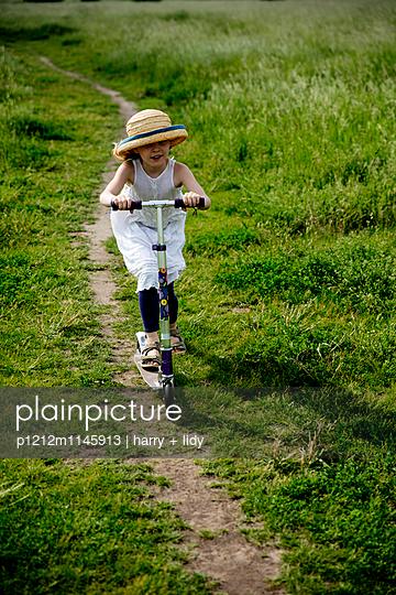 Mädchen mit einem Roller auf einem Feldweg - p1212m1145913 von harry + lidy