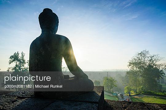 Indonesia, Java, Borobudur Temple Complex, sitting Buddha in backlight - p300m2081182 by Michael Runkel