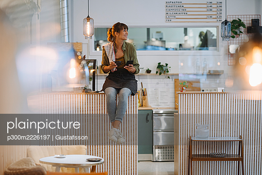 Young businesswoman holding coffee looking away using smart phone sitting on counter in cafe - p300m2226197 by Gustafsson