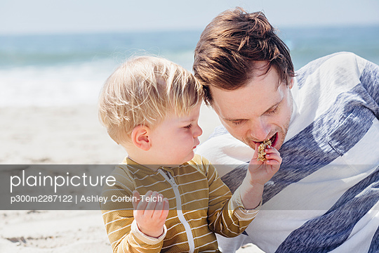 Son feeding snack to father while sitting at beach - p300m2287122 by Ashley Corbin-Teich