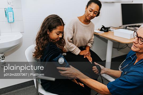 Doctor checking girls blood pressure - p312m2237367 by Plattform