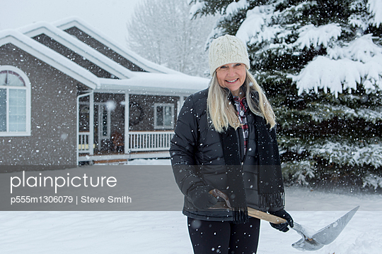 Older Caucasian woman shoveling snow in front yard - p555m1306079 by Steve Smith