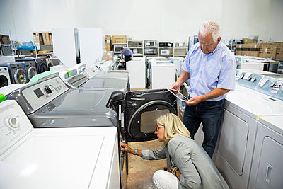 Senior couple with digital tablet shopping for clothes washer in appliance store - p1192m1158316 by Hero Images