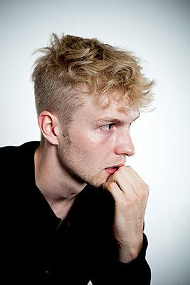 Junger Mann mit ängstlichem, sorgenvollem Gesichtsausdruck - p1195m1466340 von Kathrin Brunnhofer