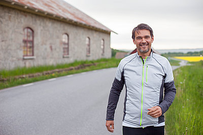 Smiling man in sports clothes - p312m1472440 by Christina Strehlow