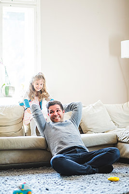 Cheerful father and daughter playing in living room at home - p426m2127425 by Maskot