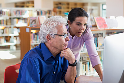Older Hispanic woman helping man using computer in library - p555m1491114 by Marc Romanelli