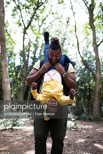 Playful father holding daughter upside down on hike in woods - p1023m2238544 by Tom Merton
