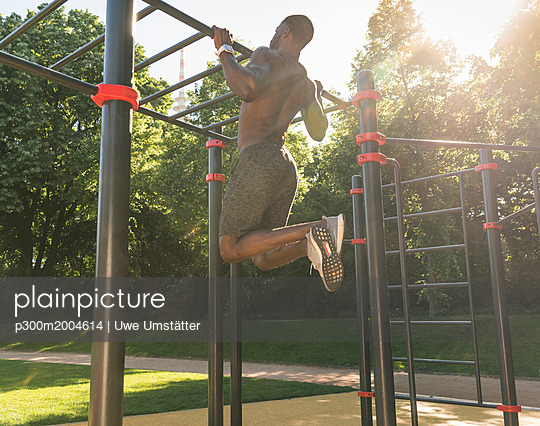 Muscular young man exercising on parcours bars - p300m2004614 von Uwe Umstätter