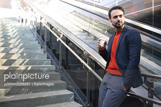 Confident entrepreneur drinking coffee while standing on staircase in city - p300m2226251 by Epiximages