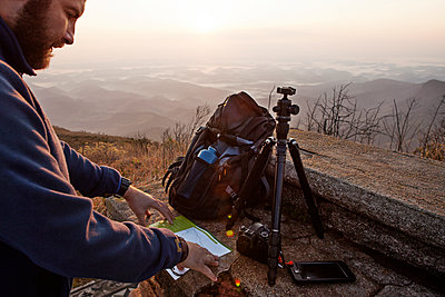 Man reading at map while standing on mountain during sunset - p1166m1174501 by Cavan Images